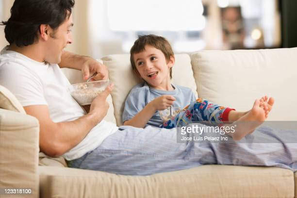 Caucasian father and son eating cereal together on sofa
