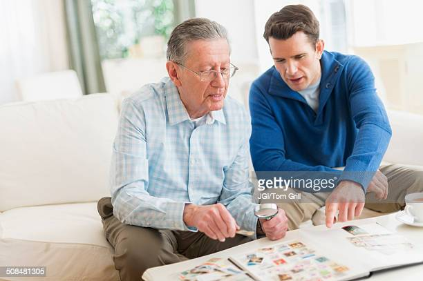 Caucasian father and son examining stamp collection
