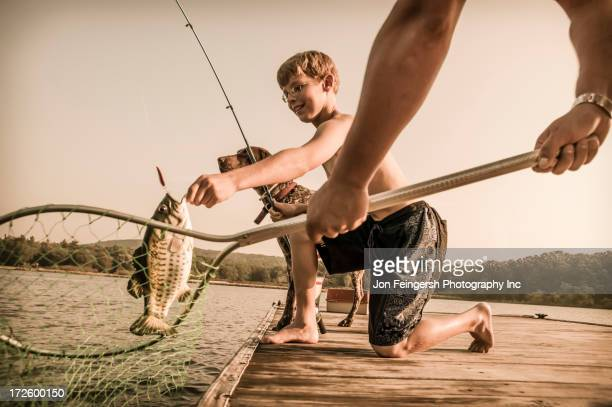 Caucasian father and son fishing with nets