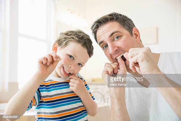 Caucasian father and son flossing their teeth