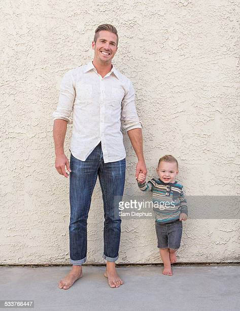 Caucasian father and son holding hands outdoors