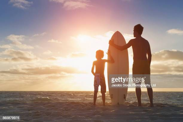 Caucasian father and son holding surfboard on beach