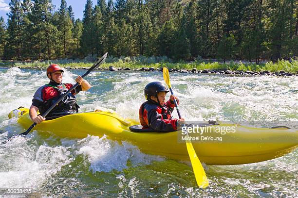 caucasian father and son kayaking in river - kajak stock-fotos und bilder
