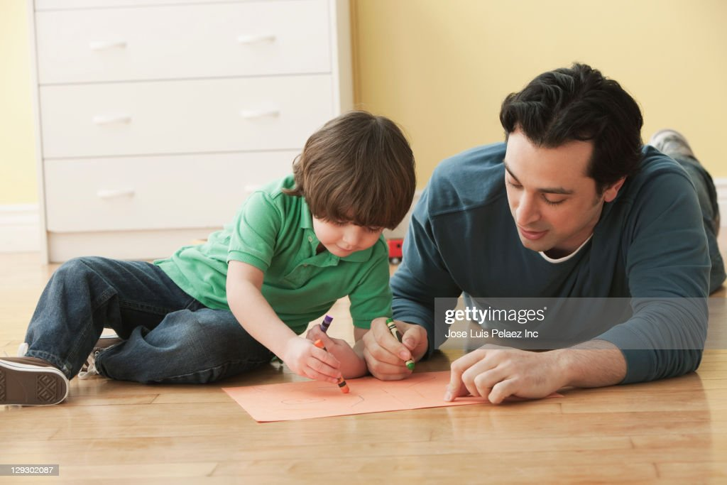 Caucasian Father And Son Laying On Floor Drawing Stock Photo
