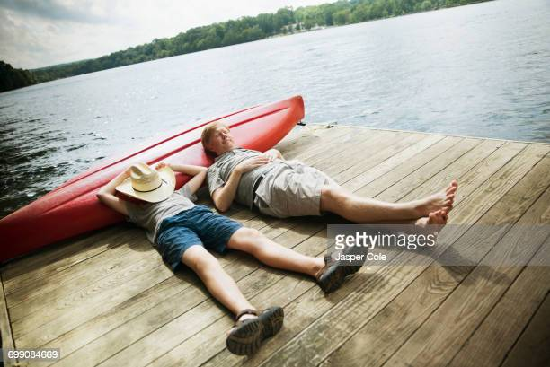 Caucasian father and son laying on wooden dock