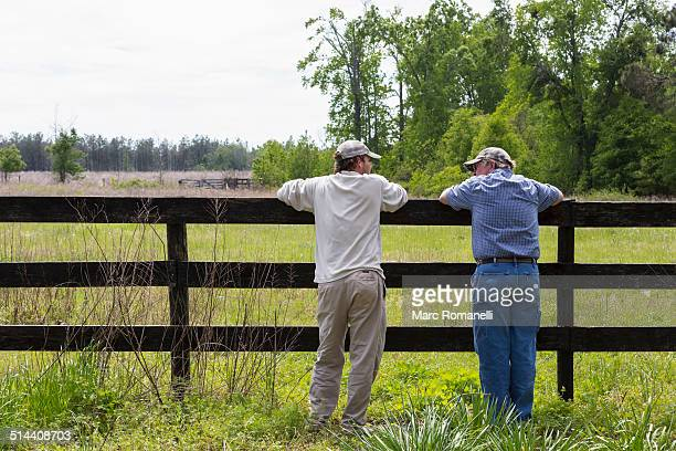caucasian father and son leaning on fence by rural field - georgia stati uniti meridionali foto e immagini stock