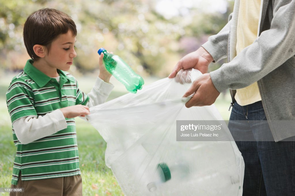 Caucasian father and son picking up litter together : Stock Photo