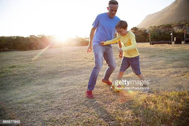 Caucasian father and son playing soccer in field