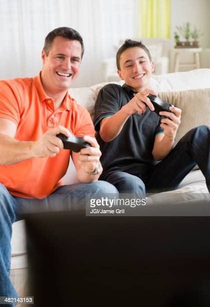 Caucasian father and son playing video games in living room