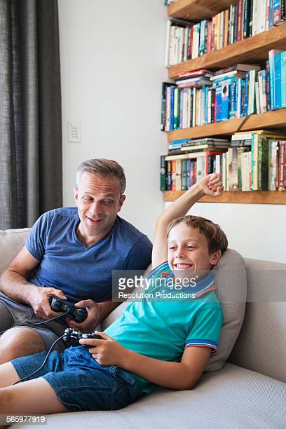 Caucasian father and son playing video games on sofa