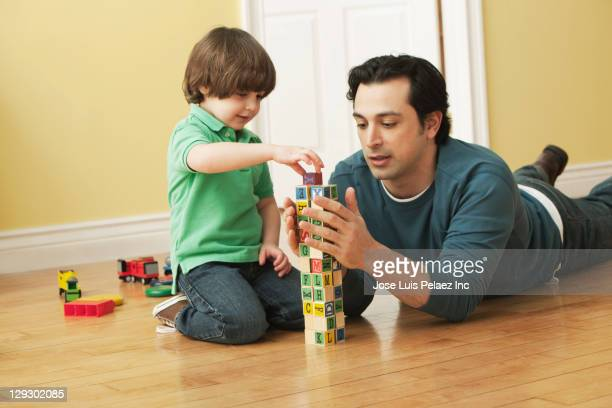 Caucasian father and son playing with alphabet blocks