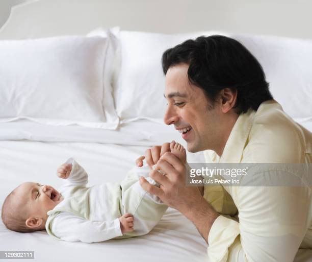 Caucasian father and son playing with baby son