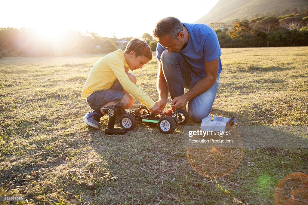 Caucasian father and son playing with remote control cars in field : Stock Photo