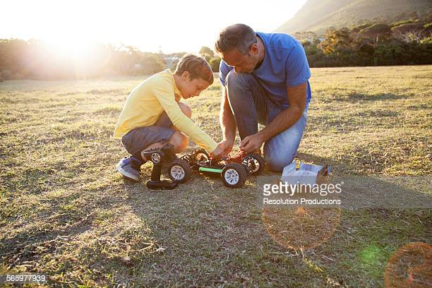 Caucasian father and son playing with remote control cars in field