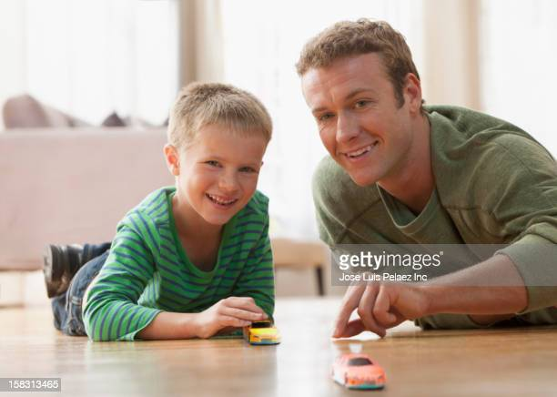 Caucasian father and son playing with toy car on floor