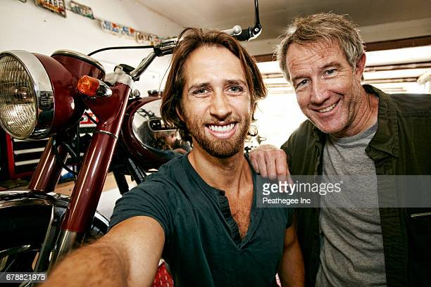 Caucasian father and son posing for selfie with motorcycle in garage