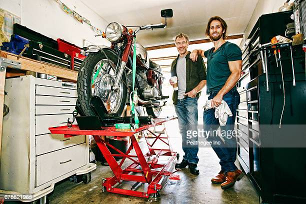 Caucasian father and son repairing motorcycle in garage