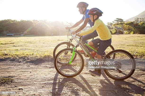 Caucasian father and son riding bicycles on dirt path