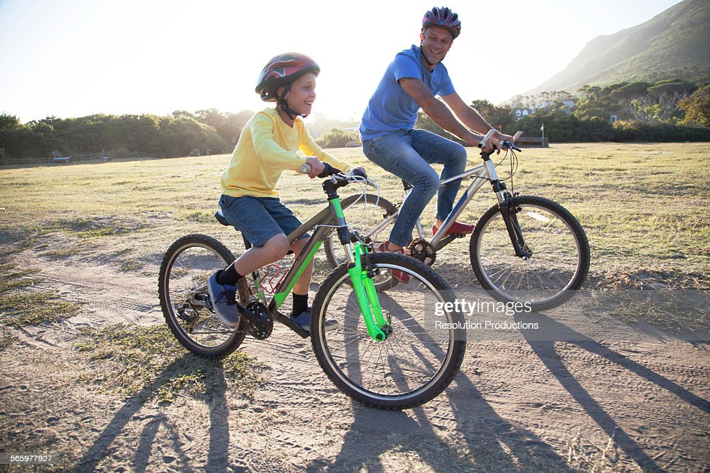 Caucasian father and son riding bicycles on dirt path : Stock-Foto