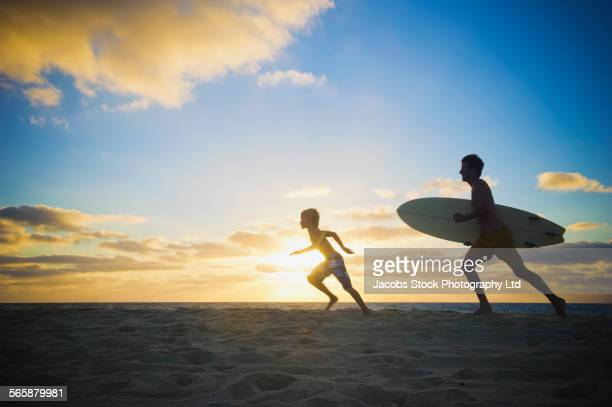 Caucasian father and son running with surfboard on beach