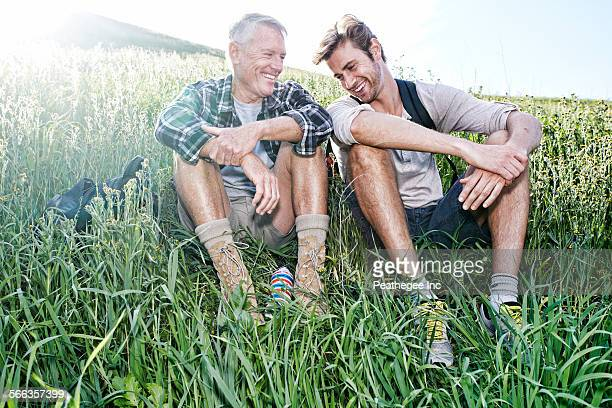 Caucasian father and son sitting on grassy hillside