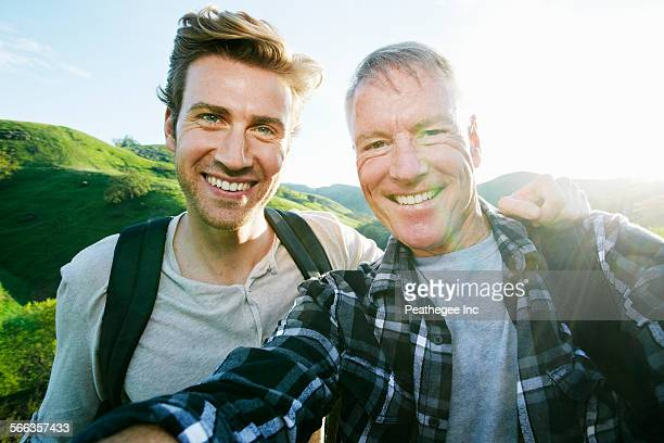 Caucasian father and son taking selfie on rural hilltop