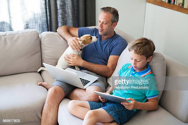 Caucasian father and son using technology on sofa