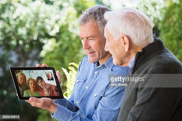 Caucasian father and son video chatting with family