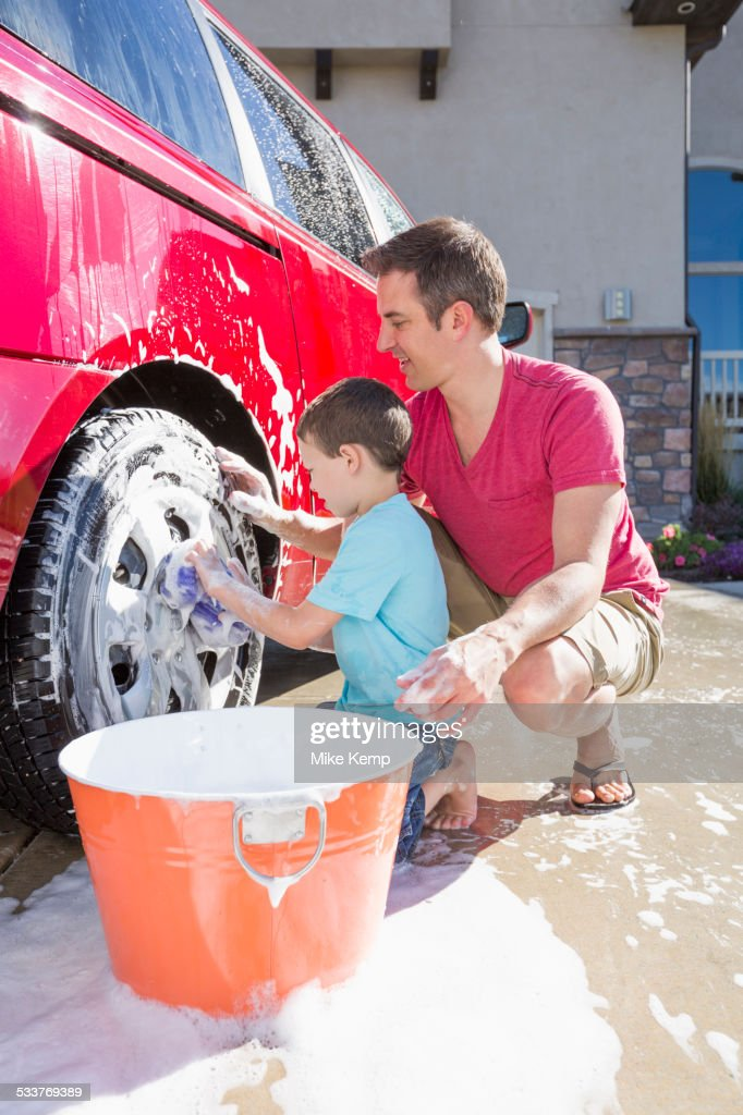 Caucasian father and son washing car in driveway : Foto stock