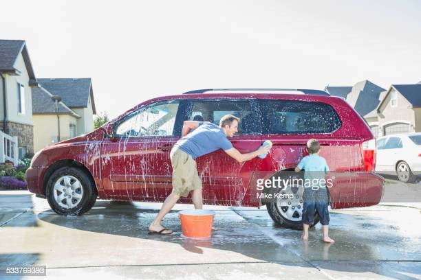 caucasian father and son washing car in driveway - mini van stock photos and pictures