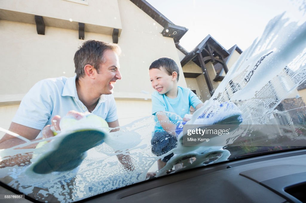 Caucasian father and son washing car windshield : Foto stock