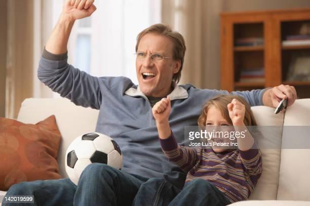 Caucasian father and son watching television