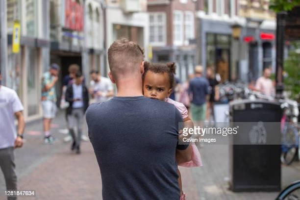a caucasian father carries his daughter through the streets of utrecht - color blindness - fotografias e filmes do acervo