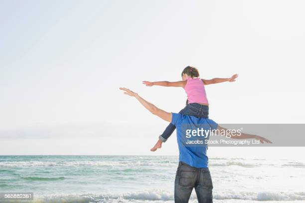 Caucasian father carrying flying daughter on shoulders on beach