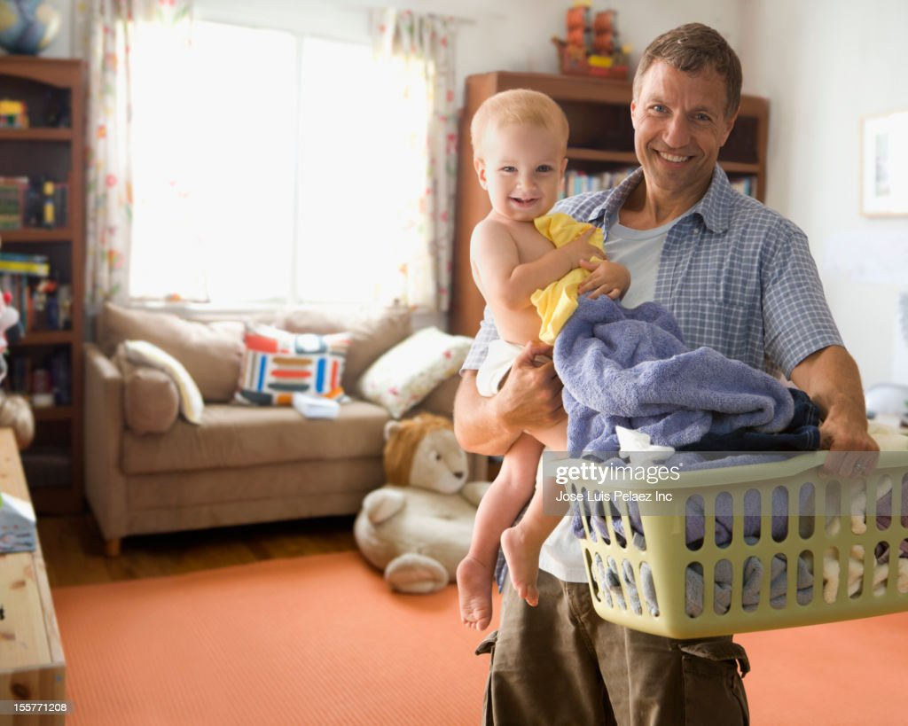 Caucasian father carrying son and laundry : Stock Photo
