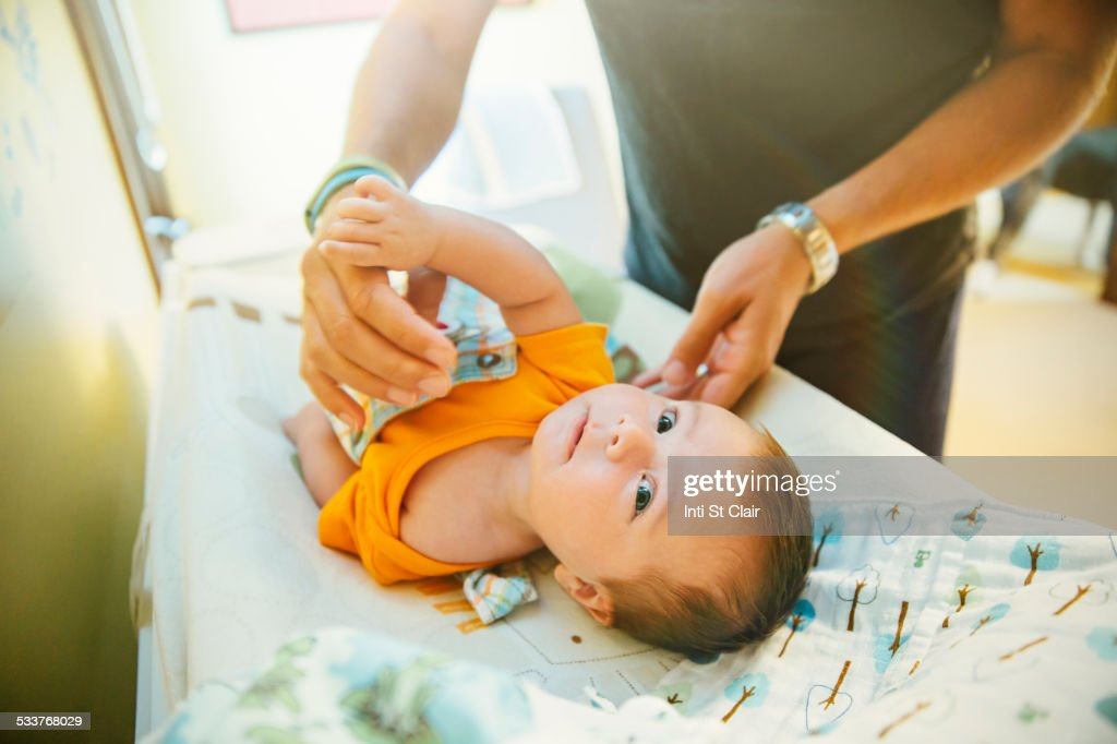 Caucasian father changing diaper of baby boy : Foto stock