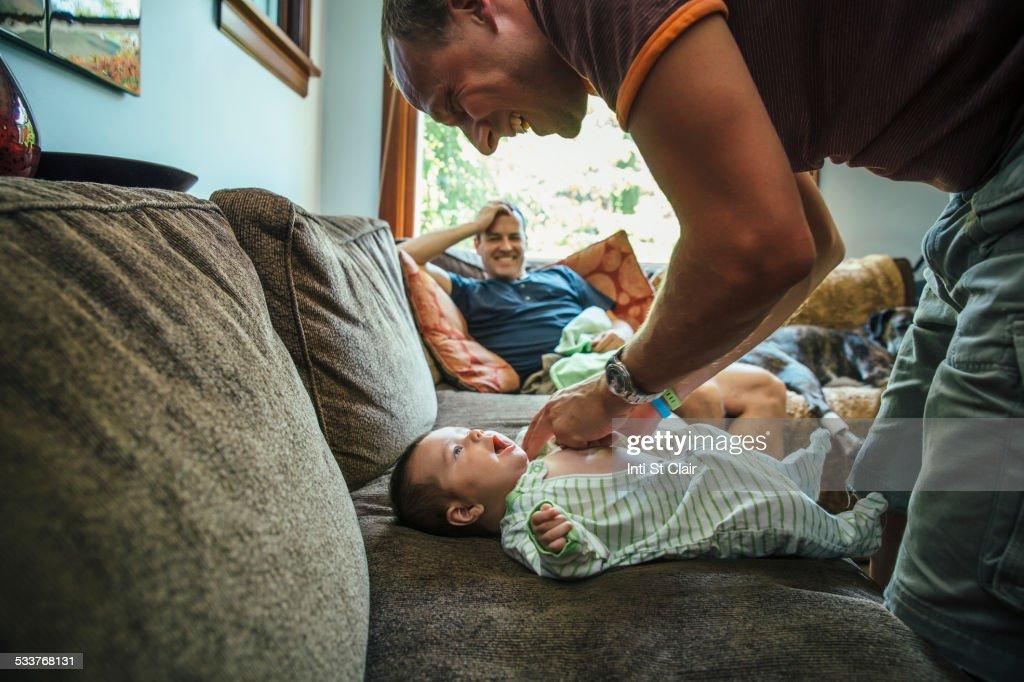 Caucasian father dressing baby boy on sofa : Foto stock