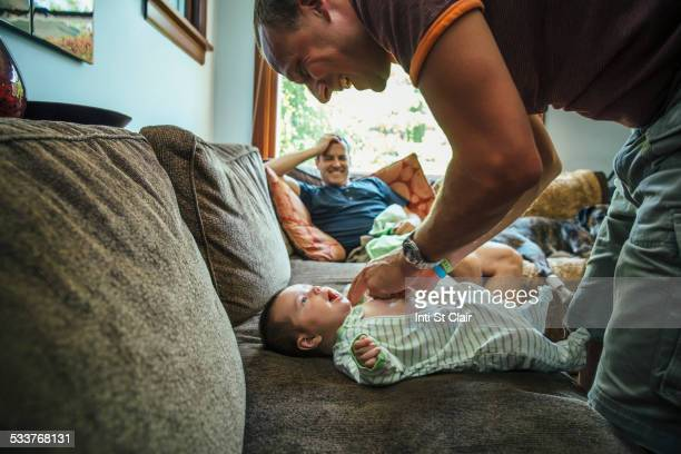 Caucasian father dressing baby boy on sofa