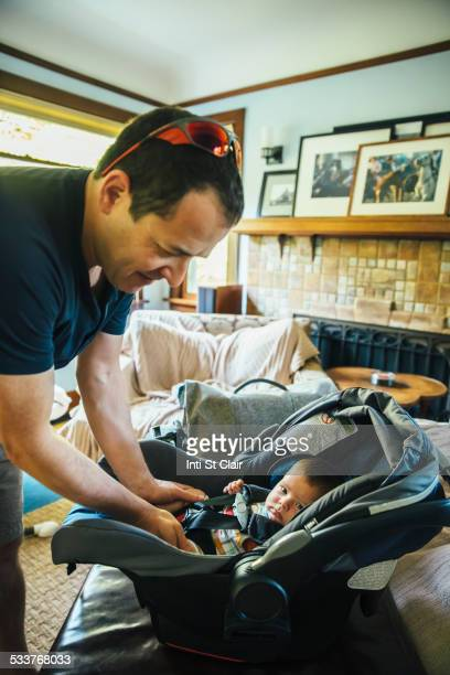 Caucasian father fastening baby boy in car seat