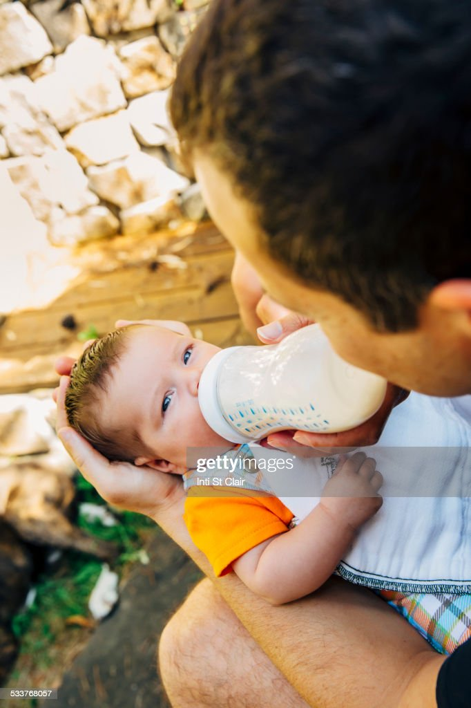 Caucasian father feeding baby boy outdoors : Foto stock