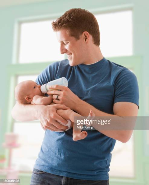 Caucasian father feeding baby girl