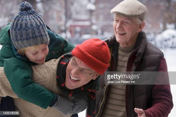 Caucasian father giving son piggy back ride through snow