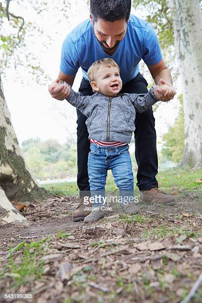 Caucasian father helping baby son walk outdoors