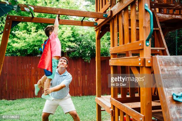Caucasian father helping superhero son hanging on monkey bars