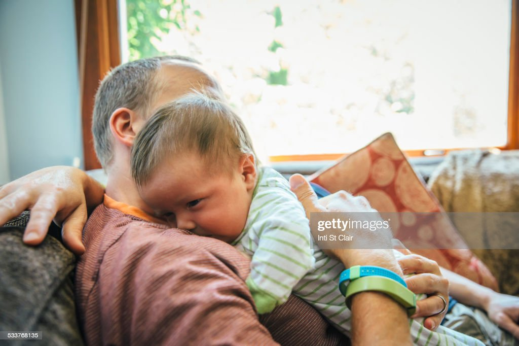 Caucasian father holding baby boy on sofa : Foto stock
