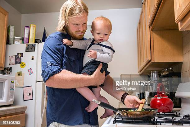 Caucasian father holding son and cooking