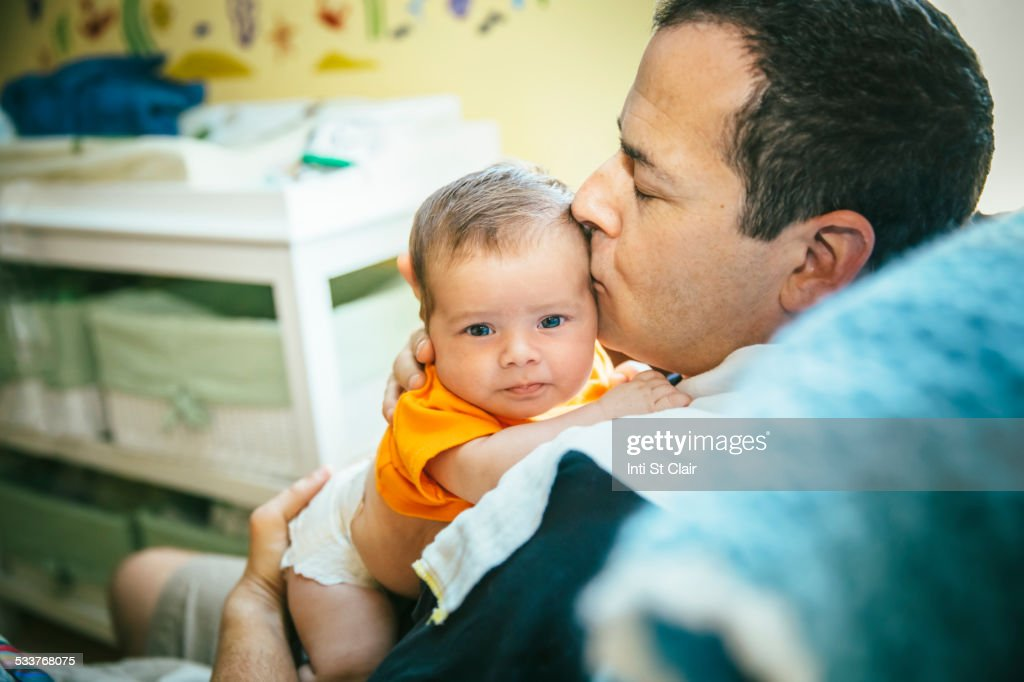 Caucasian father kissing baby boy in nursery : Foto stock