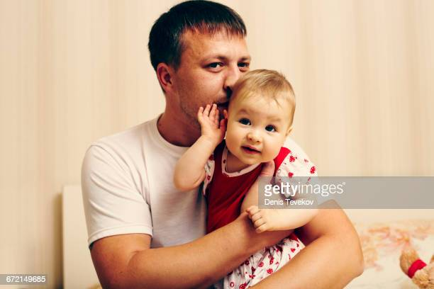 Caucasian father kissing baby daughter