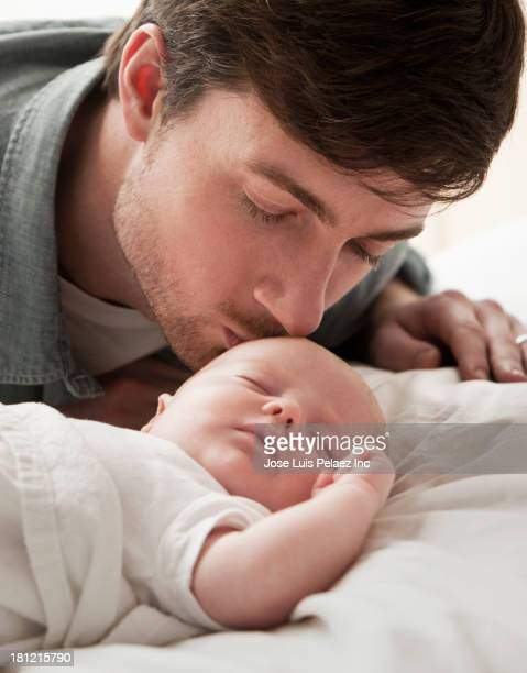 Caucasian father kissing baby on bed