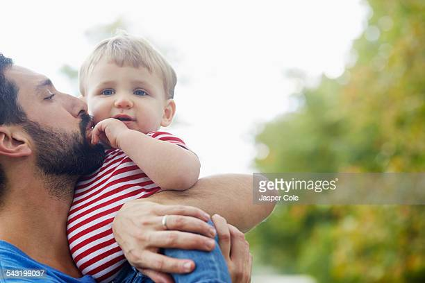 caucasian father kissing baby son - leanintogether stock pictures, royalty-free photos & images